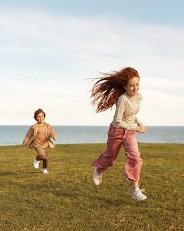 屋外で走っているフルショットの子供たち