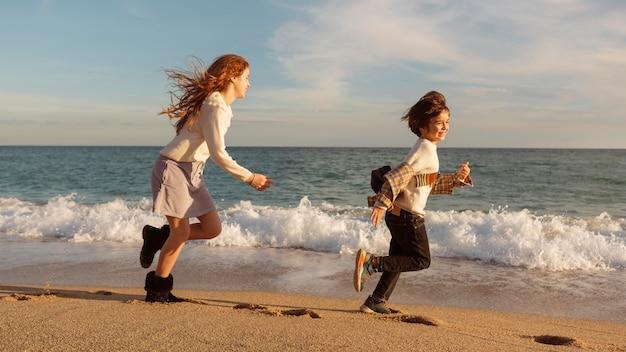 岸で一緒に走っているフルショットの子供たち