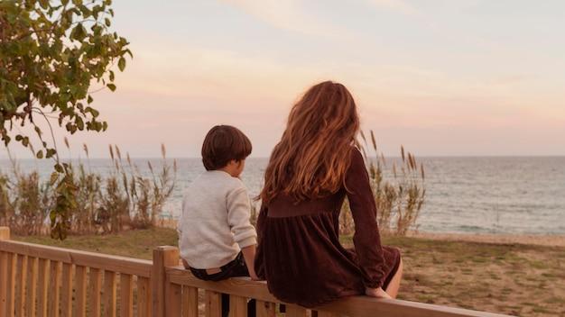 Полный снимок дети сидят на заборе вместе