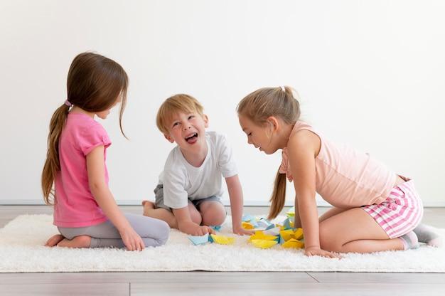 Bambini a tutto campo con barchette di carta