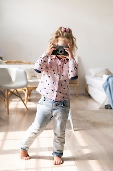 Full shot little girl taking pictures with camera