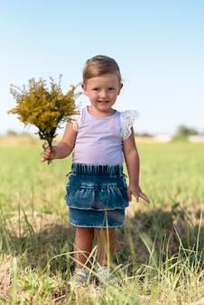 Full shot of a little girls holding a bouquet