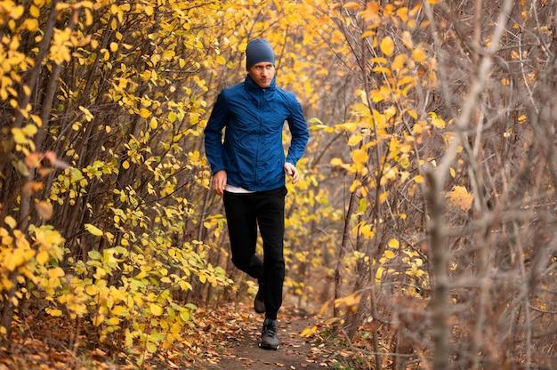 Полный снимок мужчины, бегущего по тропе в лесу