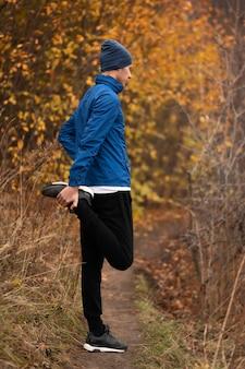 Полный снимок мужчины, растягивая ноги в лесу