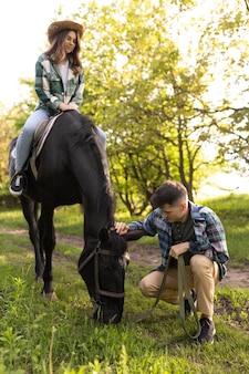 Полный выстрел мужчина и женщина с лошадью