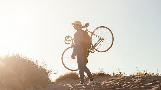 自転車を運ぶフルショットの男