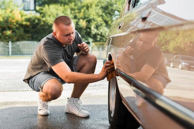 Полный выстрел человек, чистящий колесо автомобиля