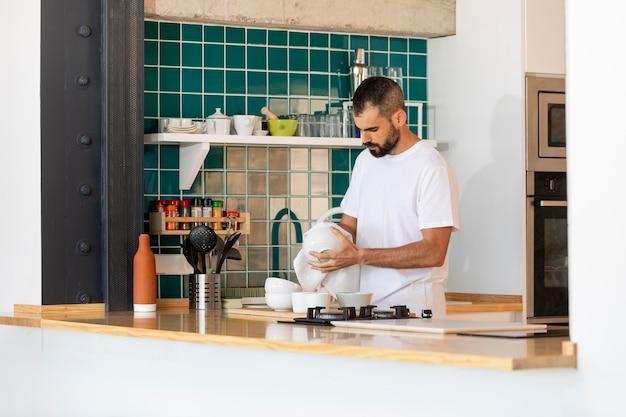 Full shot man cleaning dish at home