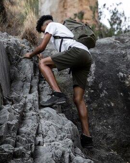 Full shot man climbing rock