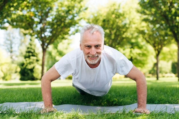 Full shot man doing push-ups outdoors