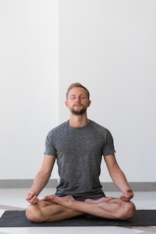 Full shot man doing sukhasana pose indoor