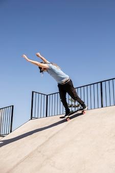 Full shot man doing trick on skate