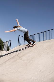 Полный кадр человек делает трюки в скейтпарке