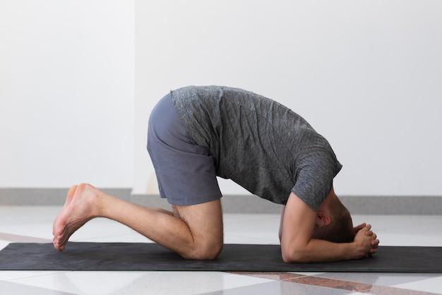 Uomo pieno del colpo che fa posa di yoga dell'interno