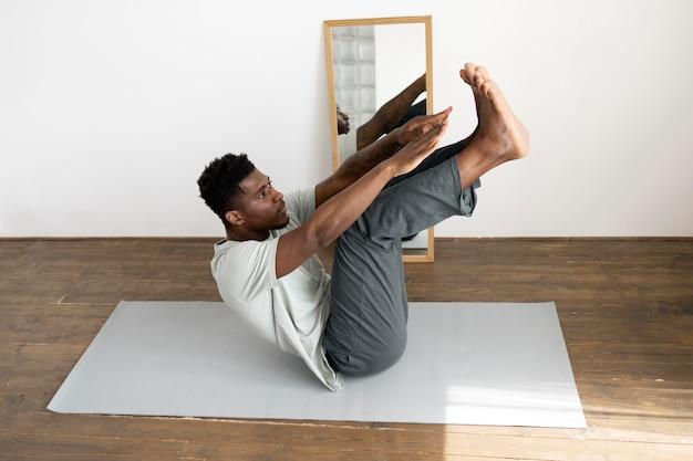 Full shot man exercising on mat