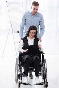 Donna d'aiuto dell'uomo della foto a figura intera in sedia a rotelle