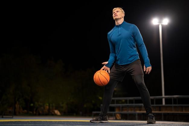 外でバスケットボールを保持しているフルショットの男