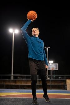 Полный выстрел мужчина держит баскетбольный мяч