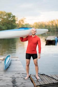 Full shot man holding canoe on shoulder