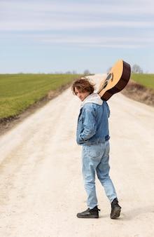 ギターを持っているフルショットの男