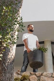 植木鉢を保持しているフルショットの男