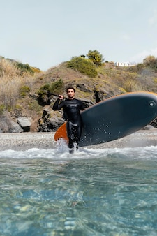 Полный выстрел мужчина держит доску для серфинга Бесплатные Фотографии