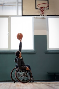 Full shot man holding up basketball