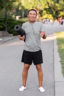 Полный выстрел мужчина держит коврик для йоги