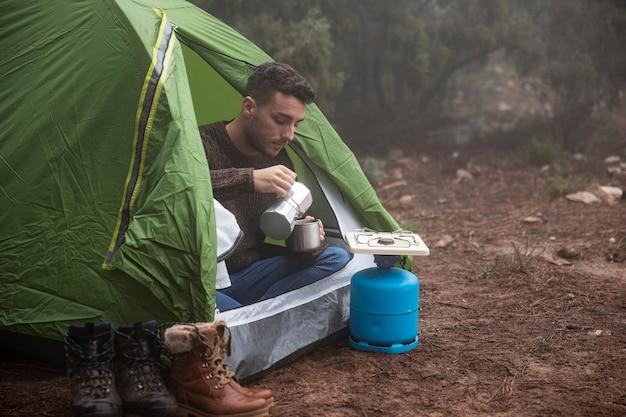 マグカップとテントの中でフルショット男