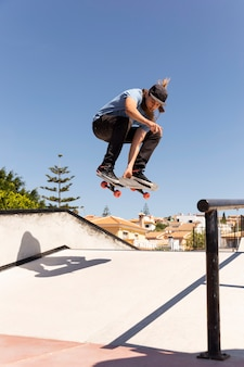 Полный выстрел человек высоко прыгает со скейтбордом