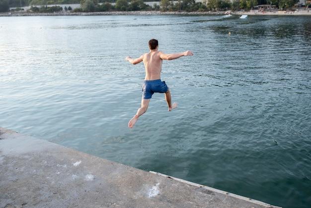 水の後ろのビューでジャンプするフルショットの男