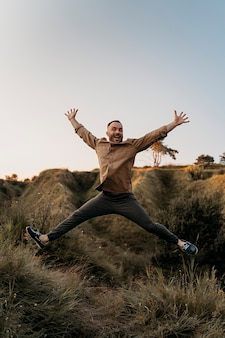 Full shot man jumping outdoors