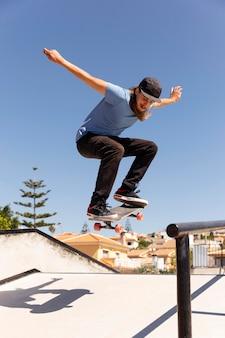 Полный выстрел человек прыгает со скейтбордом