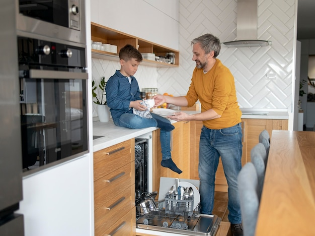 Full shot man and kid cleaning dishes