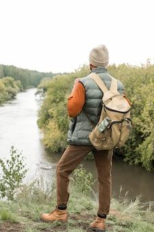 Full shot man looking at river