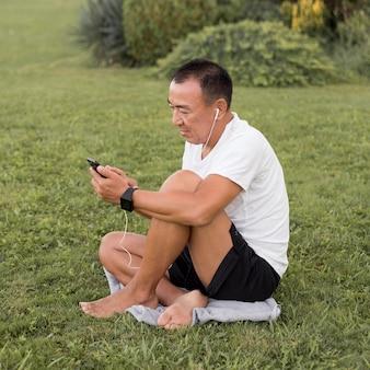 Uomo pieno del colpo che esamina smartphone