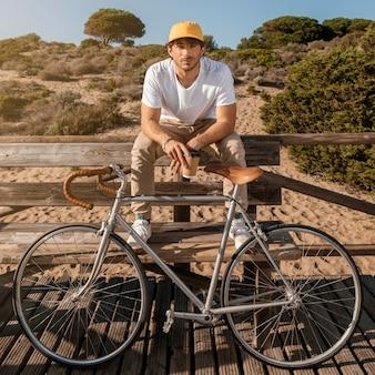 자전거와 함께 벤치에 전체 샷된 남자