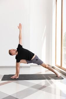 Человек в полный рост на коврике, практикующий позу йоги