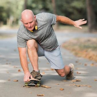 Полный мужчина на скейтборде