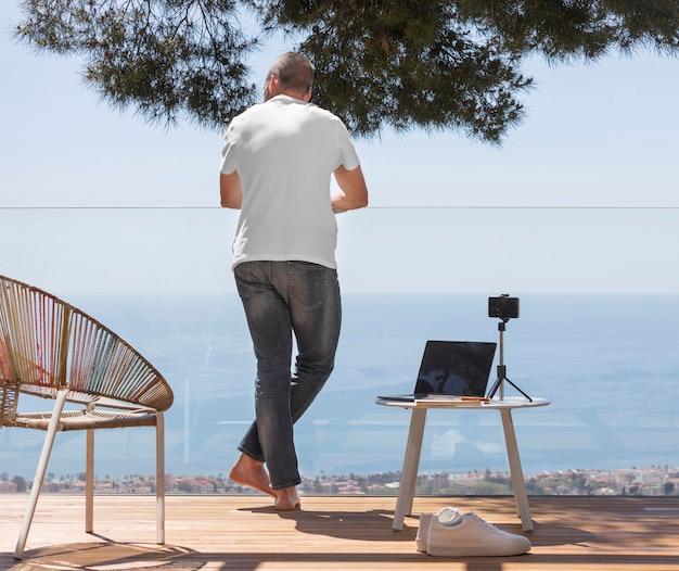 Uomo pieno del colpo all'aperto con il computer portatile
