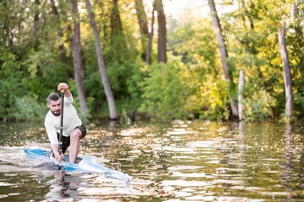Full shot man paddling