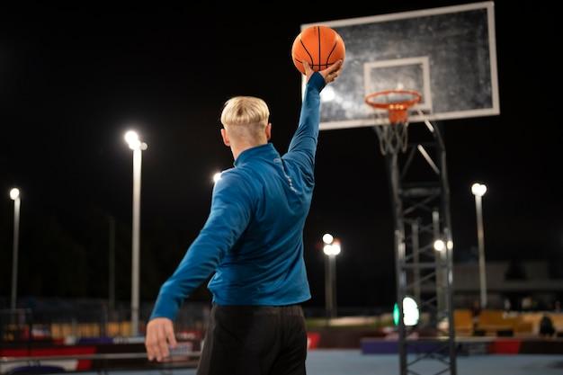 夜にバスケットボールをするフルショットの男