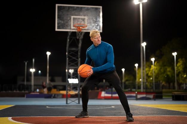 Полный мужчина играет в баскетбол