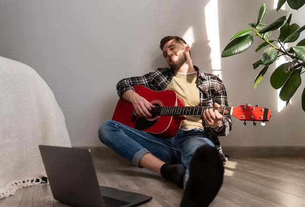 Uomo pieno del colpo che gioca la chitarra