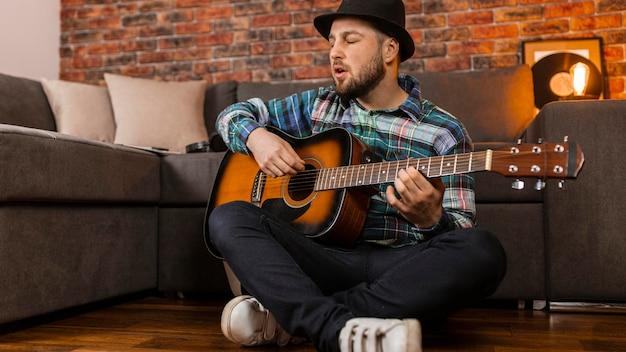 床でギターを弾くフルショットの男