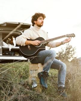 ギターを弾くフルショットの男