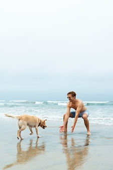 Full shot man playing with dog