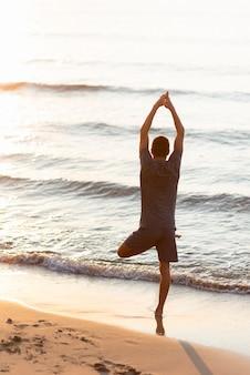 Мужчина в полный рост практикует позу дерева к морю и солнцу