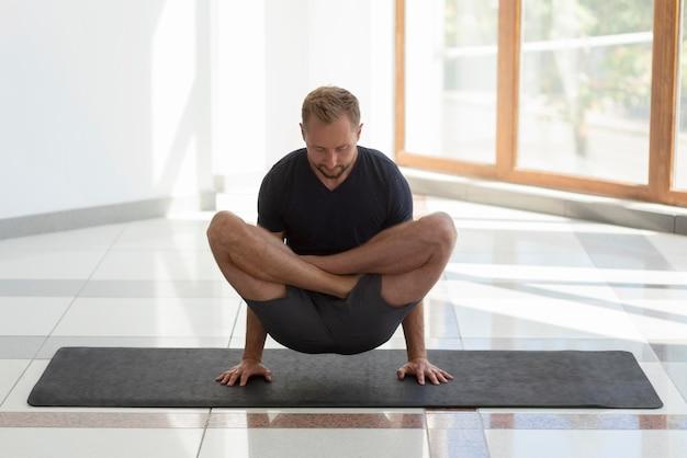 Full shot man practicing yoga indoor