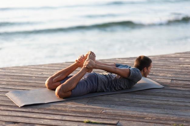 Full shot man practicing yoga pose near sea